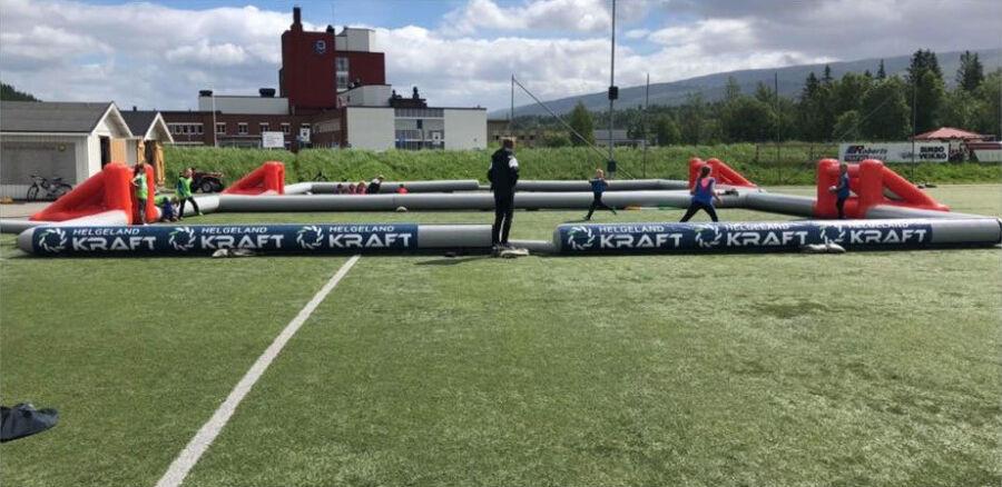 Oppblasbar 3-er fotballbane i bruk med sponsor helgeland kraft reklame banner